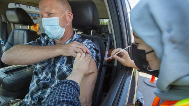 masked man in car receives a needle from a health-care worker