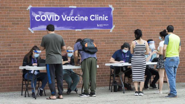 people line up at a table with a covid vaccination sign