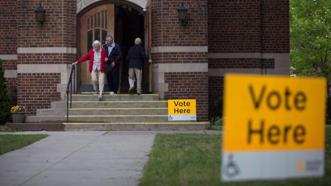 """people enter and leave a church serving as a voting location, with yellow """"vote here"""" signs"""