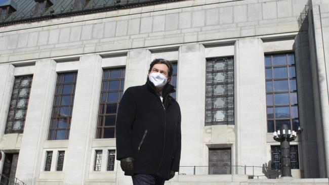 masked man in black coat stands in front of stone building
