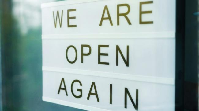 "Sign behind a glass door of a cafe that says ""we are open again."""
