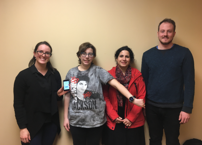 Four people, three women and a tall man, stand in a line, showing off a smart phone and a wearable watch.