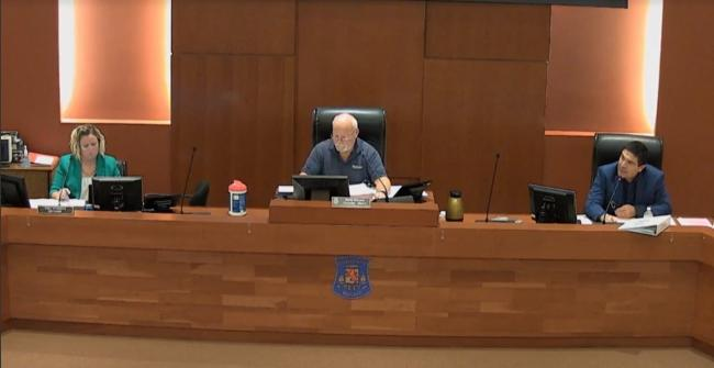 three people behind a desk in a council chamber