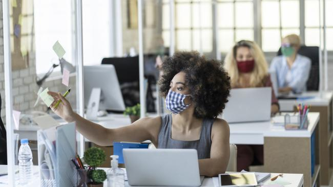 masked woman at a laptop with two colleagues sitting at desks behind her