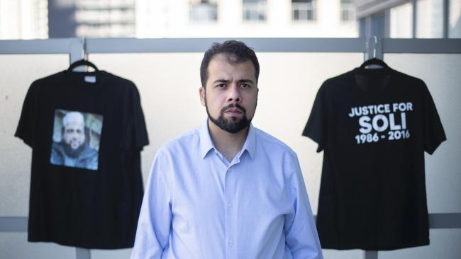 bearded man in blue shirt standing in front of two black t-shirts