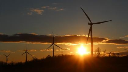 wind turbines in a field at sunset from the article Climate Roundup: Record-breaking heat as Canada's emissions keep climbing