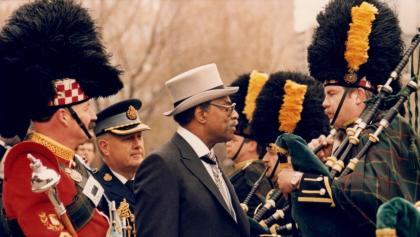man in hat and suit inspects honour guard playing bagpipes from the article The legendary Lincoln Alexander gets his due