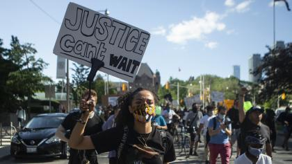 """masked protestor carrying a sign reading """"justice can't wait"""" from the article Trust issues: What Canada's new government will face on immigration and systemic racism"""