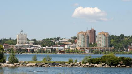 buildings behind a lake from the article How one Ontario city is tackling homelessness and the opioid crisis