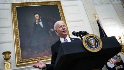 a man speaks from a podium in front of a large portrait from the article What will a Joe Biden presidency mean for us during COVID-19?