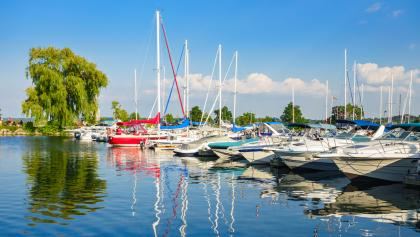 a row of boats moored on a lake on a sunny day from the article Why you should care about golfers and boat owners