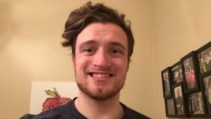headshot of a smiling man in a living room from the article 'Labour is labour': Why Hamilton students are fighting for a living wage