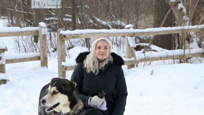 a woman stands in the snow with her dog from the article Nature is reeling: What happens when more Ontarians head outdoors?