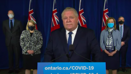 a group of masked people stand on a stage in front of flags from the article Ontario can't fight COVID-19 without more social supports. So where are they?
