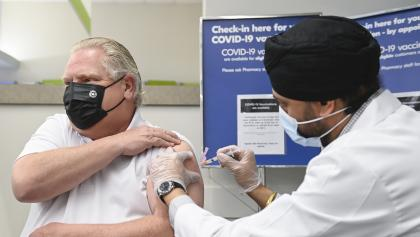 masked man rolls up sleeve to receive a needle from a masked man in a white jacket from the article Please put a shot of AstraZeneca in my arm