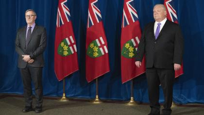 two men stand in front of four flags from the article Ontario's leaders need to tell us what's guiding their pandemic response