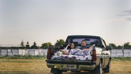 Couple in the back of a pickup truck from the article Summer at the drive-in during COVID-19
