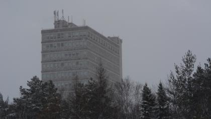 a tall concrete building behind snowy trees from the article 'Everybody was crying': How Laurentian is restructuring — and what happens next