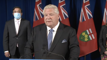 two men (one masked) in suits stand in front of flags from the article Caution and cautious optimism are a good look for Doug Ford
