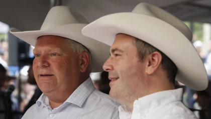 close-up of two men wearing cowboy hats from the article Alberta is in trouble. But it cleared a bar that Ontario couldn't