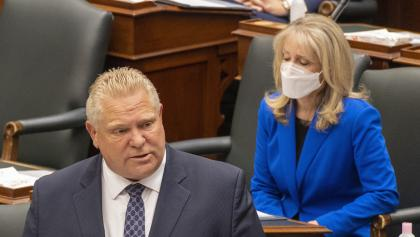 man in suit and tie talks while a masked woman in blue sits behind him from the article Ford and Fullerton should face consequences for Ontario's LTC disaster
