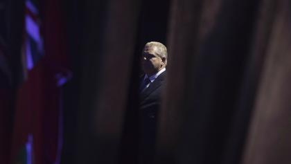 a man stands in shadow behind opened curtains from the article Doug Ford is pulling a vanishing act — again