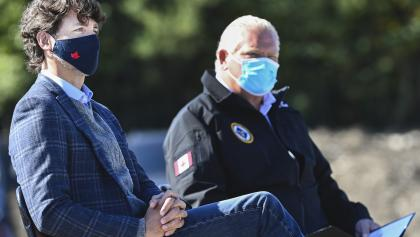 two men seating side by side wearing masks from the article Forget the carbon tax: COVID-19 testing is the latest failure of federalism