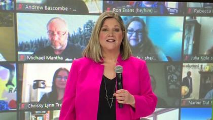 a woman in a pink jacket holding a microphone in front of a wall of video chats from the article The NDP vs. Greens showdown is on