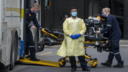 man in PPE in front of paramedics loading gurney into a bus from the article Carrots for vaccination are great. But we're likely going to need sticks, too