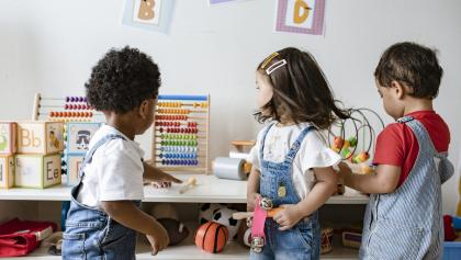 three children playing with toys from the article Home child care should be affordable, high-quality — and licensed