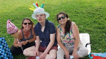 two women and young man wearing a birthday hat from the article In Ontario group homes, who counts as an essential visitor — and who should?