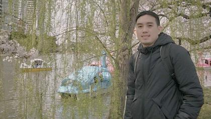 a man stands near a tree and water with paddleboats from the article What it's like for international students graduating during COVID-19