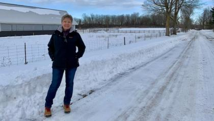 a woman stands on a snowy road in front of a fence from the article Why new prisons may not bring new jobs