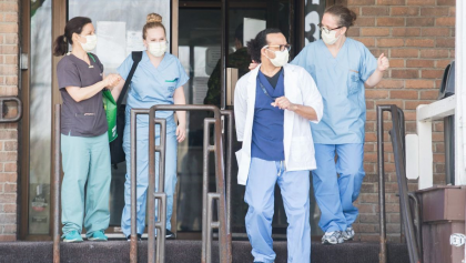 People wearing hospital scrubs and masks exit a building. from the article TVO.org daily: Tuesday, November 3