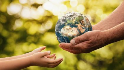 an adult handing the planet to a child from the article Excerpt: Tom Rand's 'The Case for Climate Capitalism: Economic Solutions for a Planet in Crisis'