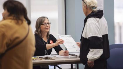 a woman hands a voter a ballot from the article 'There should be local choice': London fights to keep ranked-ballot voting
