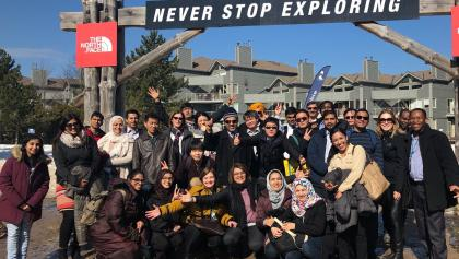 "a group of people stand in front of a sign that reads ""never stop exploring"" from the article 'In search of a more peaceful environment': Newcomers leave the GTA for new homes up north"