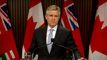 man stands behind podium from the article Finance in 2020: Ontario provides update on spending and the deficit