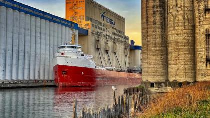 a freighter sails between two structures from the article 'Grain has saved our bacon': How Great Lakes shipping has stayed afloat during COVID-19