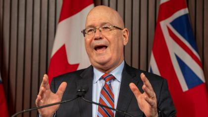 Man gestures with hands while speaking at a microphone with Ontario flags in the background. from the article What's ON: The week ahead in Ontario politics (October 18-22)