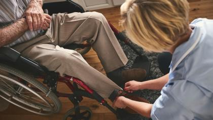 a nurse helping a man using a wheelchair from the article Why don't we know how many home-care workers have COVID-19?