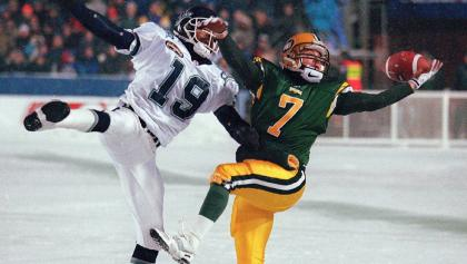 two football players trying to catch a ball from the article The Grey Cup is returning to Hamilton. What's the city's game plan?