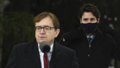 man in glasses behind a microphone in the foreground; man in black mask in the background from the article Huh? Why are the feds stepping in to review a provincial highway?