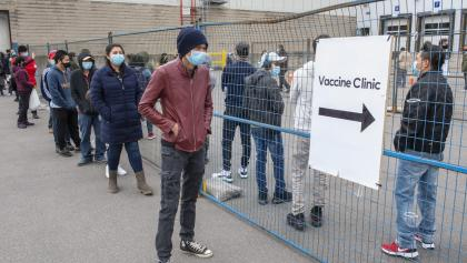 """masked people line up beside a sign reading """"vaccination clinic"""" from the article Another challenge for vaccination clinics: basic math"""