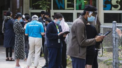 masked people stand in line from the article We need to learn from our mistakes — now — for the next pandemic