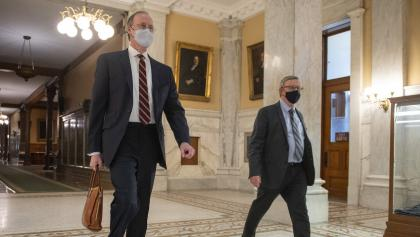 two men wearing suits and masks walk down a corridor from the article You don't need to be a doctor to know the right thing to do