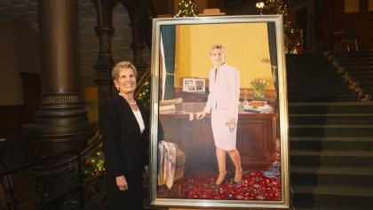 A woman stands beside a portrait from the article Why the Liberals will — and won't — miss Kathleen Wynne