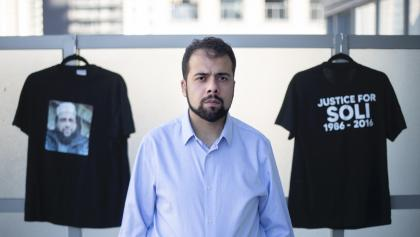 bearded man in blue shirt standing in front of two black t-shirts from the article Top Ontario official to review 'unascertained' prison death